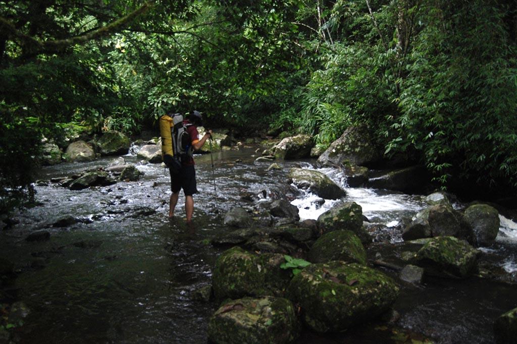 homem caminhando riacho trekking