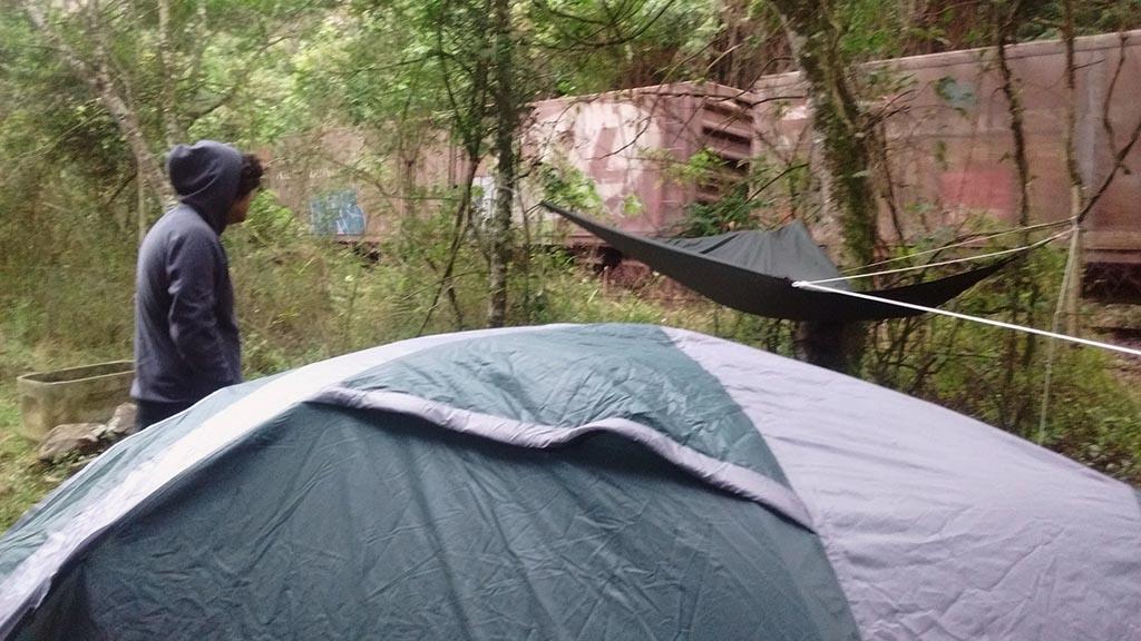 homem acampado vendo trem passar